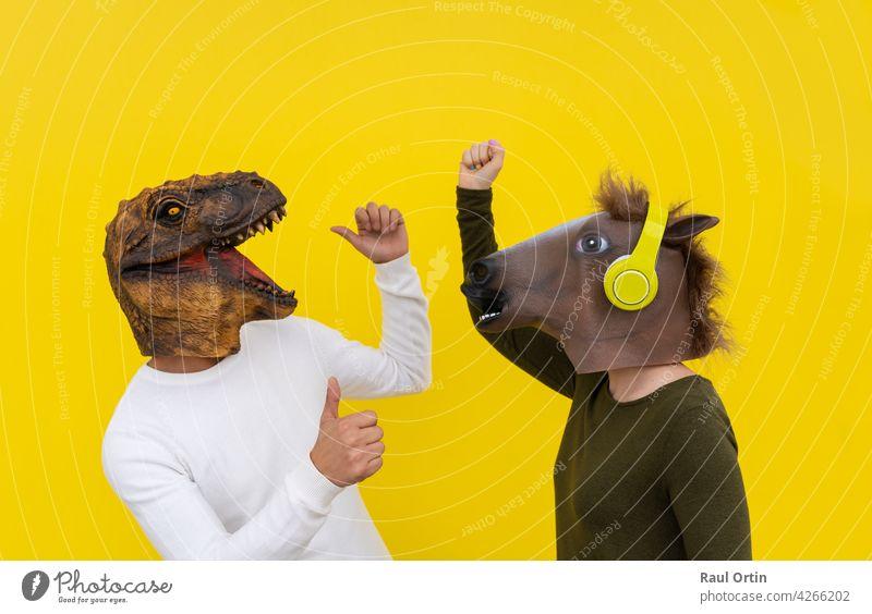 Lustiges Paar von glücklichen jungen Mann und Frau mit Dinosaurier und Pferd Kopf Maske tanzen. Positive und euphorische Menschen Lebensstil, isoliert auf gelbem Hintergrund im Studio mit leeren Wand für Kopie Raum.