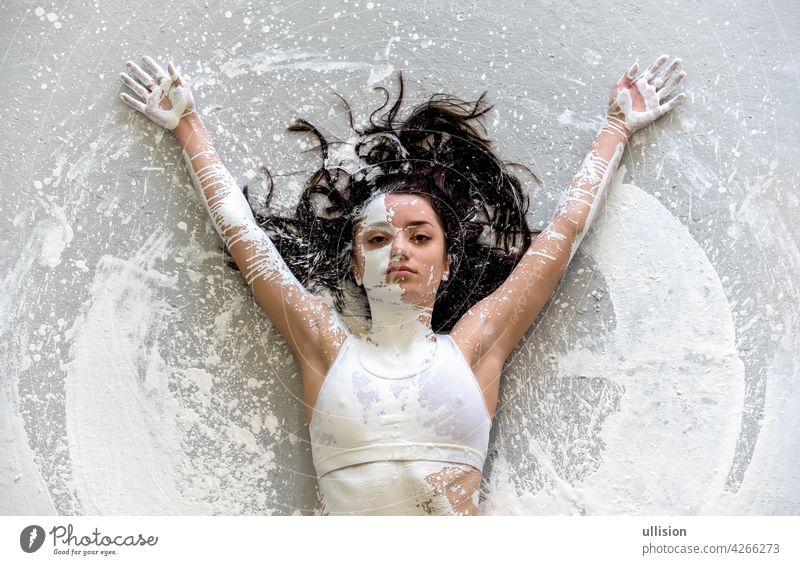 junge sexy verführerische Frau in Unterwäsche, Sportkleidung, künstlerisch abstrakt mit weißer Farbe gemalt, auf dem bemalten Boden liegend, Arme im Kreis erhoben, im Künstleratelier, Kopierraum