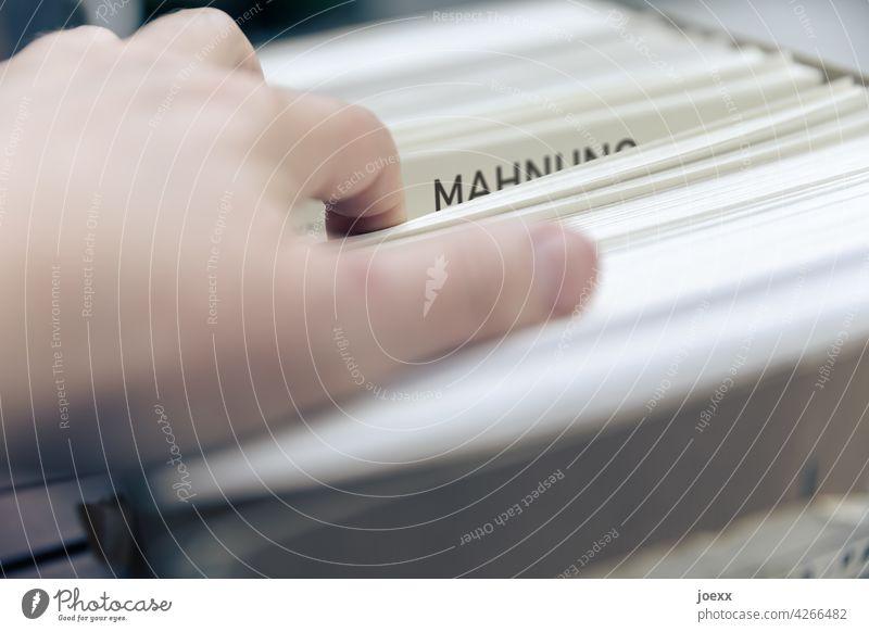 Hand an Mahnung in einem großen Papierstapel Büro Büroarbeit Schulden Zahlungsverzug bezahlen Ordnung Zettel Verzug Innenaufnahme Farbfoto suchen Sorgen