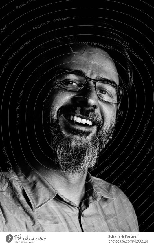 lachender Mann in schwarzweiß Bart Zähne dunkel Gesicht Portrait Schwarzweißfoto Porträt Mensch Kopf Auge maskulin Nase Mund Schatten 30-45 Jahre Hemd