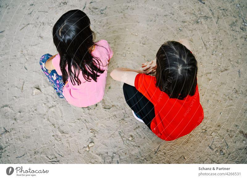 Zwei Mädchen hocken auf dem Sandboden Kinder Geschwister Schwestern Familie Hocke zusammen Strand Ausflug Familienausflug Familienleben Kindheit Freude Glück