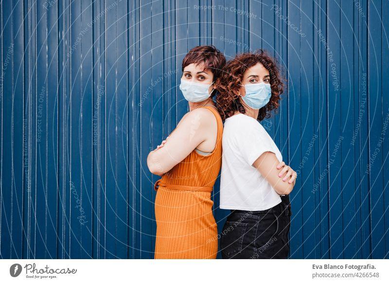 zwei kaukasische Frauen im Freien mit Gesichtsmaske, die während des Coronavirus soziale Distanz wahren Ellbogen COVID Kaukasier vermeiden Prävention Mundschutz
