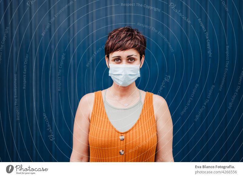 kaukasische Frau im Freien trägt Gesichtsmaske. Pandemie während Corona-Virus soziale Distanz Konzept. Kaukasier Porträt Großstadt urban Freizeitkleidung jung