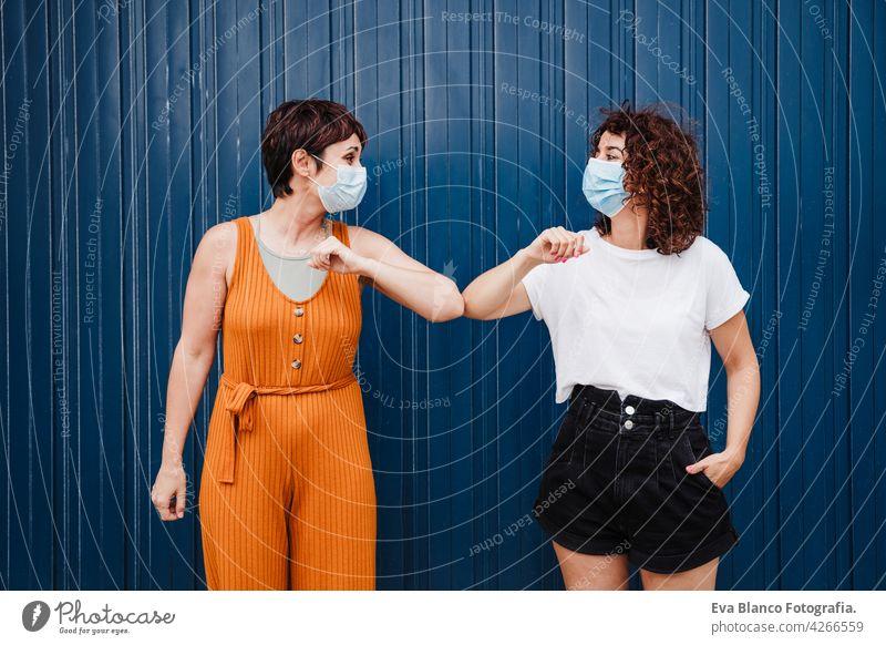 zwei kaukasischen Frauen im Freien tragen Gesichtsmaske Gruß mit Ellbogen. Pandemie während Corona-Virus sozialen Abstand Konzept. COVID Kaukasier vermeiden