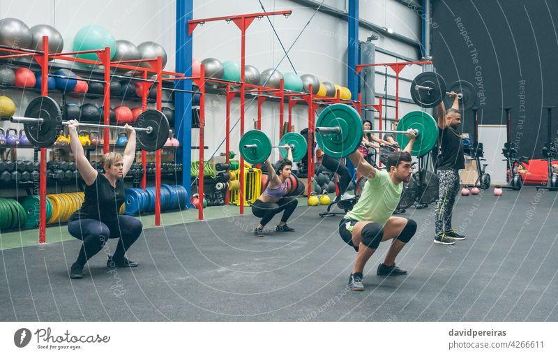 Menschen, die Gewichtheben üben und Gewichte in der Turnhalle heben Fitnessstudio Menschengruppe Heben Kurzhantel Gerät Greifen Sauberkeit Ruckeln