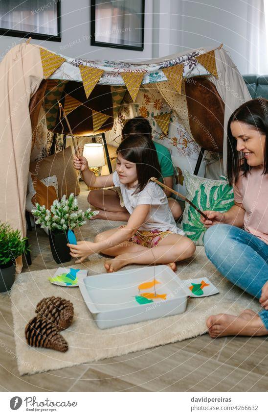 Glückliche Mutter und Tochter Camping zu Hause spielen diy Angeln Spiel Heimaturlaub diy Angelspiel Familie Spaß zu Hause Lächeln Diy-Zelt Angelrute Lager