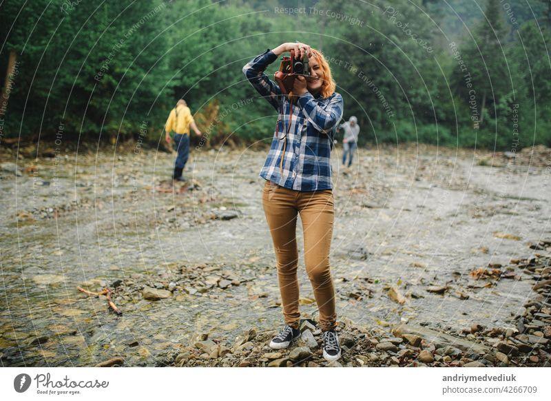 Junge rothaarige Frau mit Vintage-Kamera nimmt Foto in der Nähe des Flusses in einem Gebirge Fotokamera reisen retro jung schön Sommer Natur Fotograf Mädchen