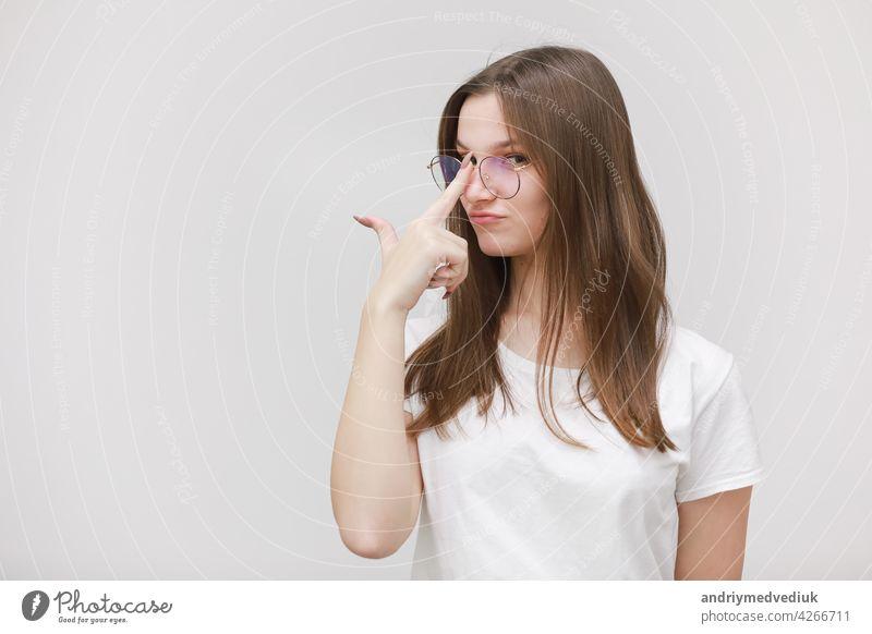 Fokussierte Stirnrunzeln Büro Mädchen starrt auf Kamera durch Brille auf weißem Hintergrund. Junge Frau, die eine Brille einstellt. Brille tragen Konzept