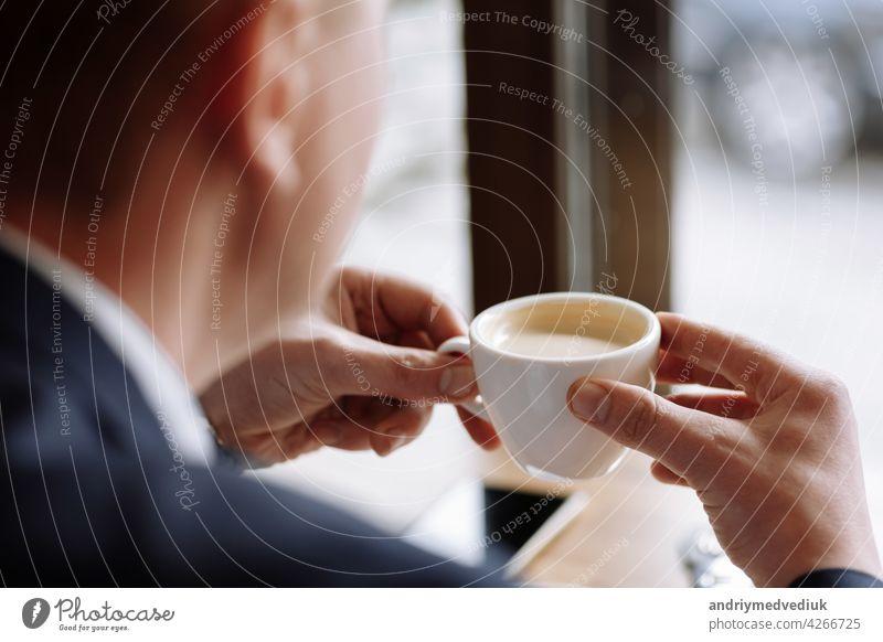 Ein Mann in einem Business-Anzug hält eine Tasse heißen Kaffee in seinen Händen. Morgen Geschäftsmann im Café.Kopieren Raum. trinken Pause männlich Frühstück