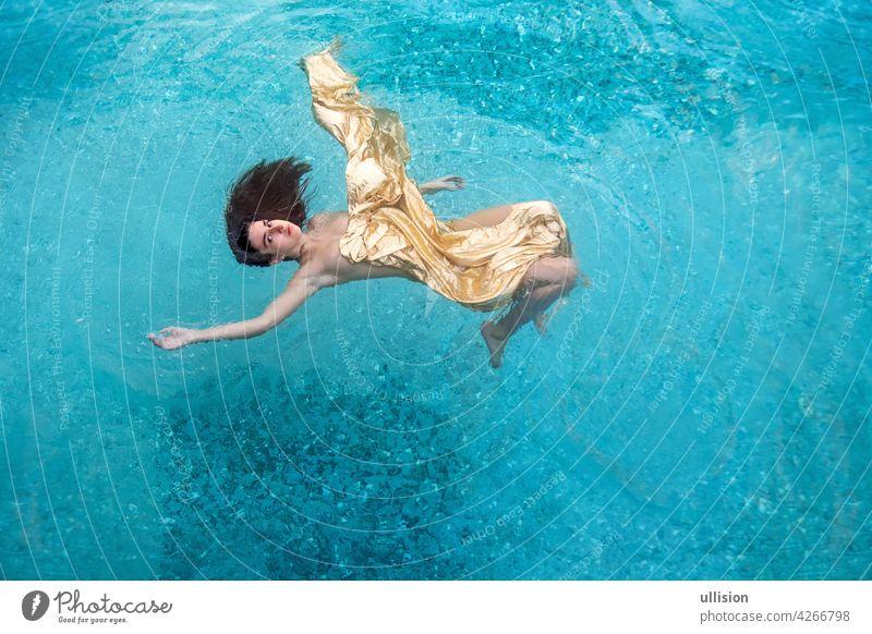 schöne sexy junge Frau Meerjungfrau in goldenen Kleid, Tuch schwimmt schwerelos elegant in der blauen türkisfarbenen Spa-Pool Wasser verträumt fliegend