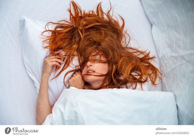 Attraktive, junge, sexy, rothaarige Frau, Rothaarige, Haare wild auf den Laken, Mund offen, liegend in frischen weißen Laken im Schlafzimmer, Hotelbett, Kopie Raum.