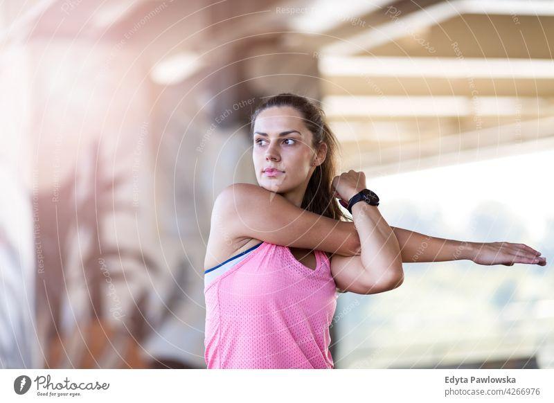 Junge Frau macht Fitness-Übung im städtischen Bereich Energie trainiert. Sport Aktivität Vitalität Körper Turnkleidung Training anstrengen beweglich