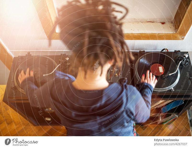 Frau Dj bei der Arbeit mit Vinyl-Schallplatten, Draufsicht jung Menschen eine Person schön Behaarung Rastalocken dj mischt Plattenteller Aufzeichnen Musik