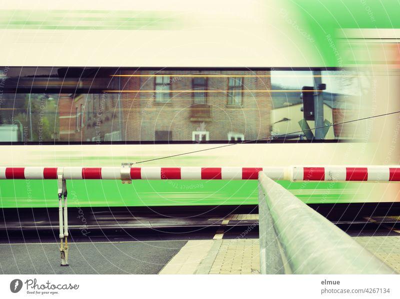 An einem geschlossenen Bahnübergang fährt ein Zug vorbei, in seinen Fenstern spiegeln sich Häuser / Bewegungsunschärfe / Reisen / Schienenverkehr Bahnfahren