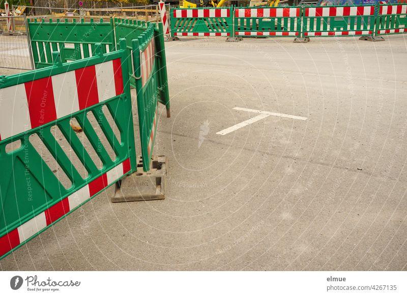 Eine Baustelle ist durch grüne Absperrbaken aus Kunststoff gesichert / Fahrbahneinengung / Bauzaun Absperrtechnik Klappbake Leitbake Fahrbahnteiler Straßenbau