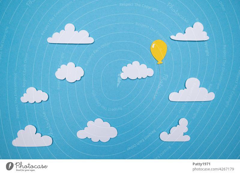 Aus Papier ausgeschnittener Luftballon schwebt alleine zwischen fluffigen Wolken durch den Himmel Lutballon einsam solo Menschenleer Einsamkeit frei Freiheit