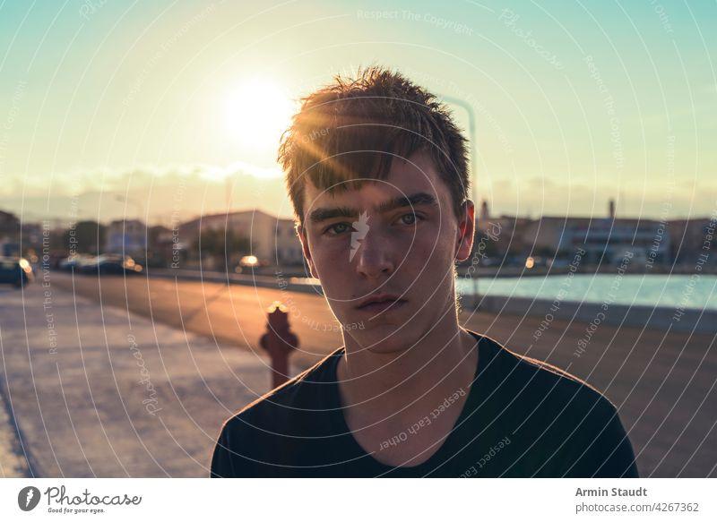 Porträt eines ernsten Teenagers mit der Sonne hinter seinem Kopf jung Mann traurig beunruhigt müde Sonnenuntergang hafen Pier hintergrundbeleuchtet Sonnenlicht