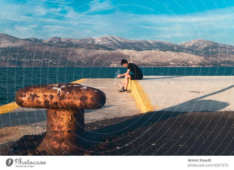 nachdenklich Teenager sitzt auf einem Pier am Meer mit schöner Landschaft im Hintergrund jung Mann Sitzen traurig ernst allein einsam Flasche Wasser hafen