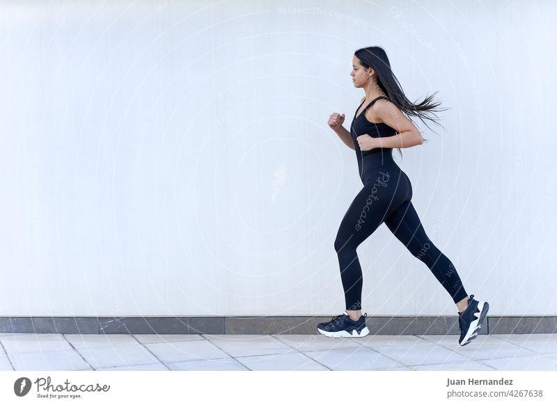 Junge Frau mit fit Körper läuft in Sportkleidung jung passen springend rennen Model Sportbekleidung trainiert. Athlet Übung Fitness Training Läufer horizontal