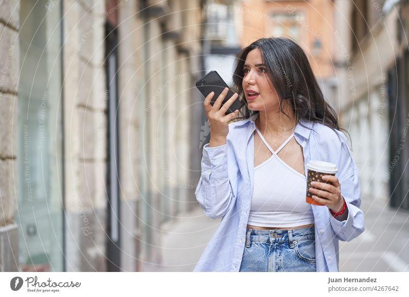 Junge Frau sendet eine Audionachricht mit Smartphone arabisch jung Senden Nachricht muslimisch Dame Handy Funktelefon ethnisch Ausdruck expressiv Kaffee Karton