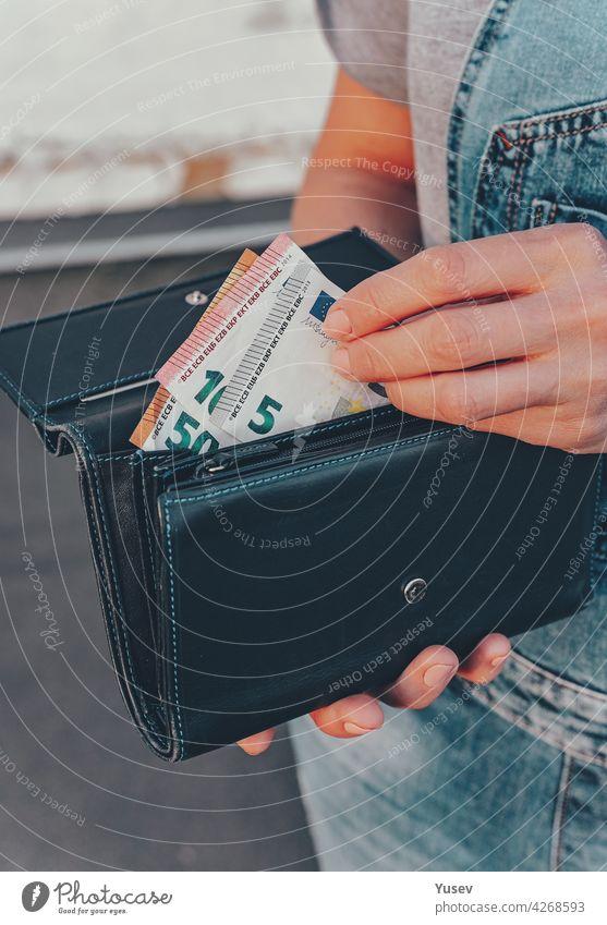 Weibliche Hände halten eine Brieftasche mit Euro-Banknoten. Das Konzept der Finanzen, Ersparnisse, finanzielle Ausgaben. Nahaufnahme. Vertikale Aufnahme Frau