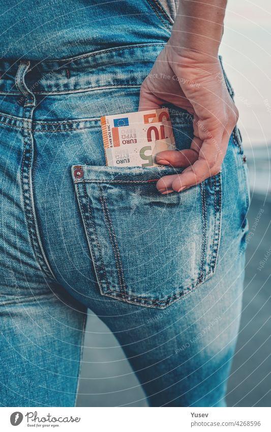 Die Hand einer Frau holt Euroscheine aus der Gesäßtasche ihrer Jeans. Das Konzept der Finanzen, Ersparnisse, finanzielle Ausgaben. Nahaufnahme unter Rechnung