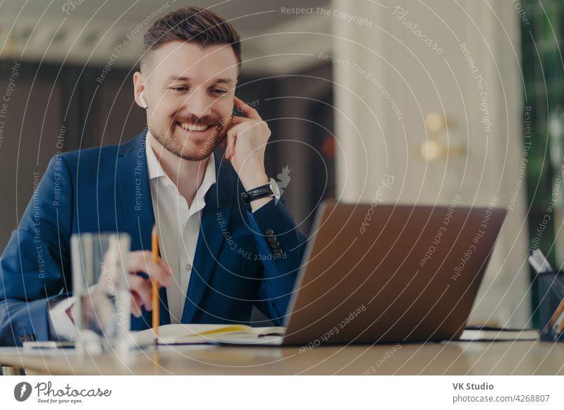 Erfolgreicher, glücklicher CEO bei einem Online-Meeting, mit Laptop und Kopfhörern Geschäftsmann Lächeln Videokonferenz Webkonferenz sprechend Büro gutaussehend