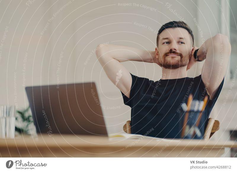 Glücklicher Geschäftsmann, der sich nach der Arbeit ausruht, während er an seinem Arbeitsplatz zu Hause sitzt Freiberufler Büroangestellte entspannt Laptop