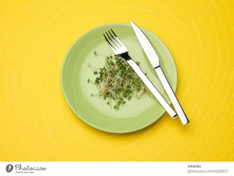 grüne Sprossen aus Chia, Rucola und Senf in einem grünen runden Teller, Ansicht von oben. Ein gesundes Essen Messer Gabel Ackerbau Transparente Biografie Diät