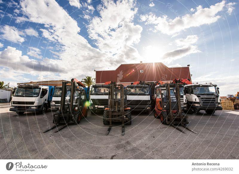 Lastwagen und Gabelstapler aufgereiht in Baufirma mit Industrielager dahinter. Weitwinkelaufnahme an einem bewölkten Tag. Konstruktion Fahrzeug Transport