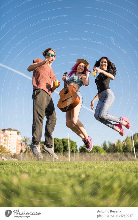 Eine Gruppe von Freunden genießt ihre Freizeit im Park, spielt Gitarre und genießt Frau jung attraktiv 20s Freude Menschen Person Jugend urban Frauen hübsch