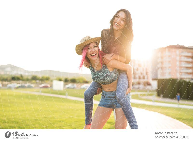 Zwei spielerische Frau spielt im Park in Sonnenuntergang Licht jung attraktiv 20s Freude Menschen Person Jugend urban Frauen hübsch hübsche Menschen im Freien