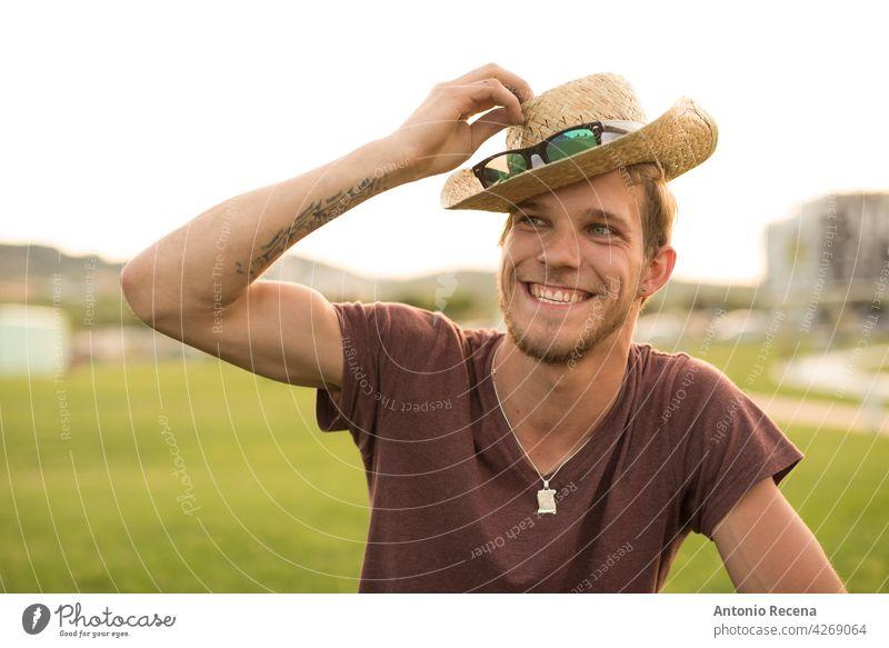 Ein junger blonder Mann rückt einen Hut bei Sonnenuntergang zurecht attraktiv 20s Freude Menschen Person Jugend urban hübsch hübsche Menschen im Freien