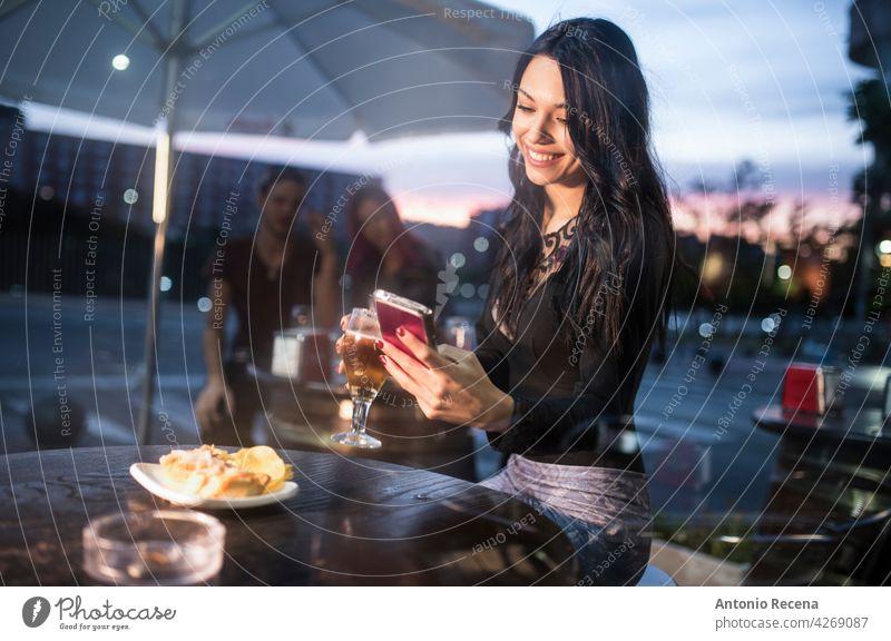 Frau schaut Smartphone in Bar Terrasse beim Bier trinken jung attraktiv 20s Freude Menschen Person Jugend urban Frauen hübsch hübsche Menschen im Freien