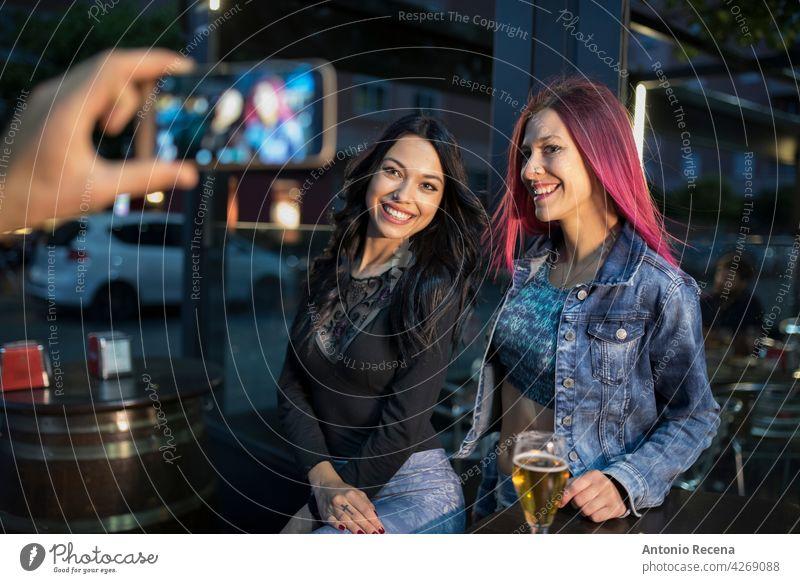 Eine Hand nehmen zwei Frauen Telefon Fotografie jung attraktiv 20s Freude Menschen Person Jugend urban hübsch hübsche Menschen im Freien Großstadt Lächeln Glück