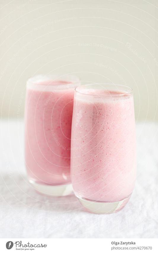 Zwei Gläser mit Erdbeermilchshake. Milchshake Erdbeeren Smoothie Beeren rosa rot melken Glas Minze kalt Sommer Tisch weiß abschließen Selektiver Fokus trinken