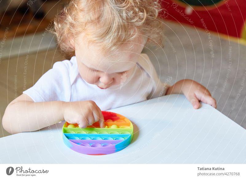 Beliebtes Anti-Stress-Spielzeug Pop It. Kind spielt mit dem Pop It Fidget Spielzeug. Glückliche Kindheit, beliebte Lernspiele. popit antistress sensorisch