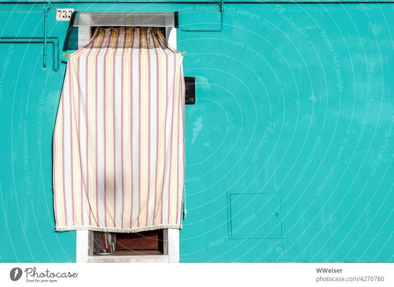Ein Vorhang spendet Schatten im Eingangsbereich dieses bunten Hauses Fassade Tür hängen Sommer heiß warm Sonnenlicht gestreift farbig türkis blau grün