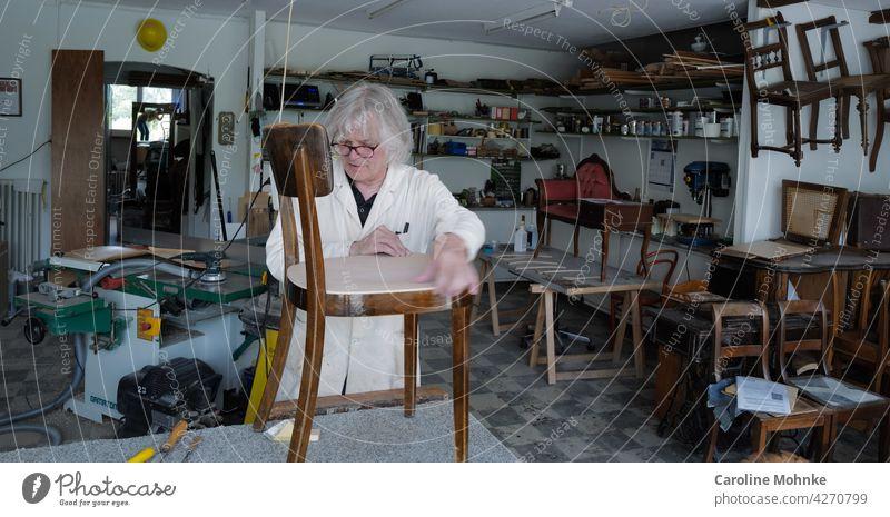 Restaurator in seiner Werkstatt arbeiten Arbeit Stühle Stuhl Antiquitäten alt Maschinen Atelier Handwerk Beruf Arbeitsplatz Herstellung Fähigkeit Meister Job