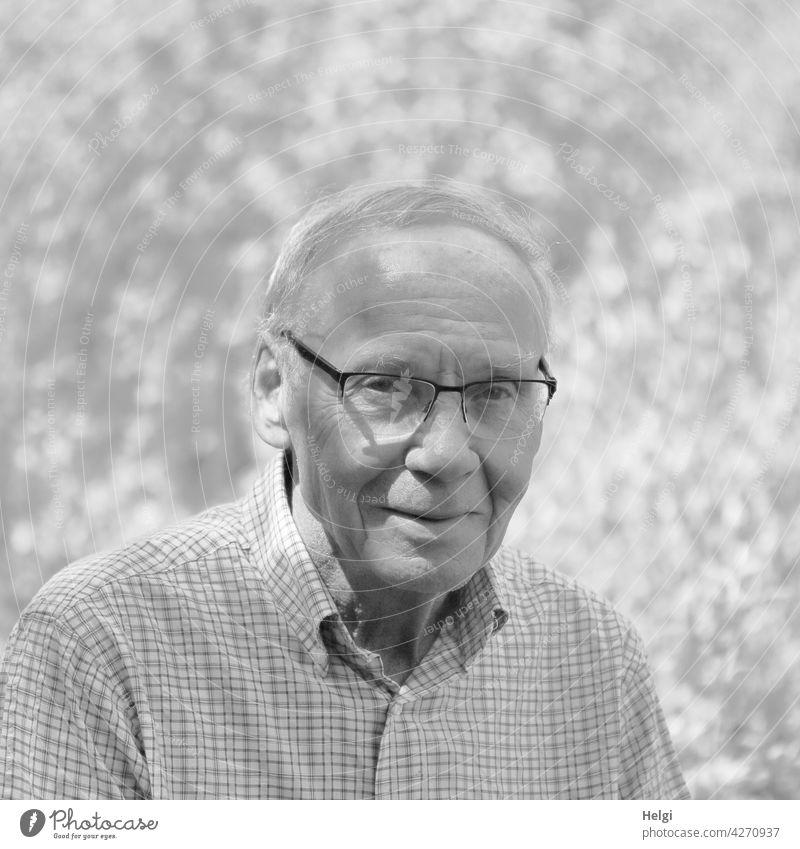 schwarz-weiß-Porträt eines freundlichen Senioren mit Brille in der Natur Mensch Mann Alter männlich Erwachsener reif alt Ruhestand Lächeln draußen lächelnd