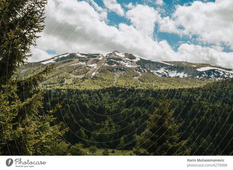 schöne Bergkette mit Schnee im Frühsommer Hintergrund blau Wolken kalt Land Landschaft Feld Wald Gras grün hoch wandern Wahrzeichen Reittier Berge u. Gebirge
