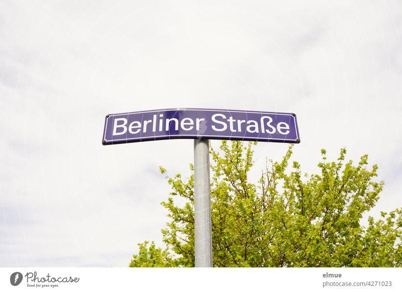 """geknicktes Straßennamenschild """" Berliner Straße """" vor einem grünen Busch und Wolkenhimmel Straßenschild Orientierung Knick beschädigt wohnen bewölkt zentral"""