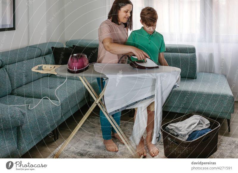 Mutter lehrt ihren Teenager-Sohn zu bügeln Lehre bügelnd heimwärts Hilfe Bügelbrett Wäschekorb Kleidung Zusammensein Wohnzimmer Hausfrau Kind Frau Menschen