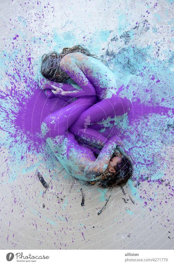 Zwei künstlerisch abstrakt gemalte junge sexy Frauen, Freundinnen in rosa, lila, türkis und weißer Farbe liegen wie ein Yin-Yang-Symbol auf dem Boden im Studio, Kopierraum.