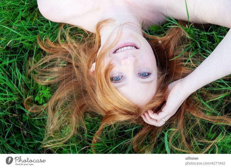 lächelndes Porträt einer schönen jungen sexy rothaarigen Frau, die rote Haare fächerförmig ausbreitet und entspannt auf dem grünen Gras liegt, auf dem Kopf stehend, Kopierraum