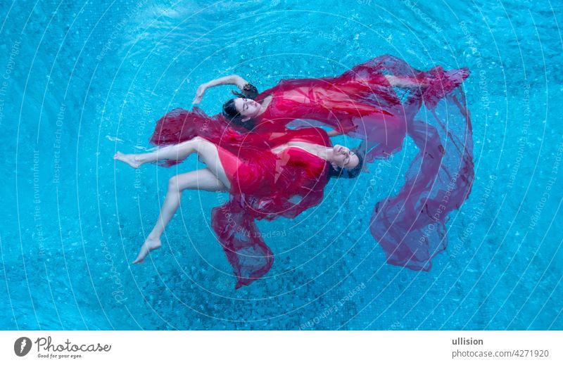 Draufsicht auf eine schöne junge sexy dunkelhaarige Frauen entspannt in rotem Kleid schweben schwerelos elegant im Wasser des Pools, Kopie Raum zwei Schwimmer