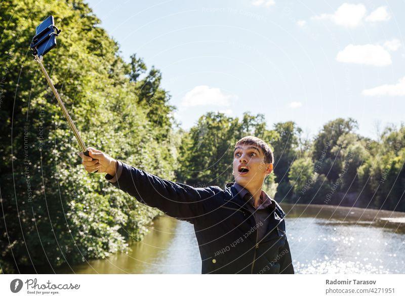 junger Mann macht Selfie mit einem Selfie-Stick männlich kleben Fotokamera Selbst Gesicht Porträt Glück Freizeit Hintergrund Person machen Smartphone Hand