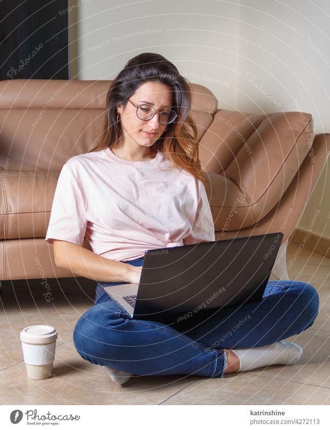 Junge Frauen verwenden einen Laptop, während sie zu Hause auf dem Boden sitzen jung anhaben Attrappe T-Shirt lernen Schüler Lifestyle Jeanshose Brille ernst