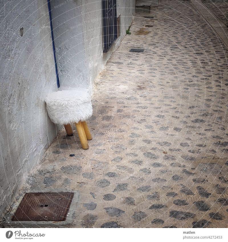 anlehnungsbeduerftig Anlehnungsbeduerftig Hocker Strasse Sitzgelegenheit Menschenleer Wand Außenaufnahme Kopfsteinpflaster Fellbezug Bein fehlend alt Fassade