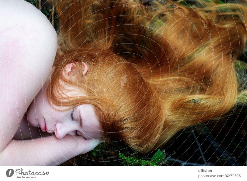 Porträt einer nackten, jungen, charmanten, sexy Frau mit rotem Haar, die im herbstlichen Wald liegt und ihre langen roten Haare um den Kopf gelegt hat.
